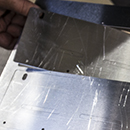 Close up on one unformed brackets being removed from the sheet metal