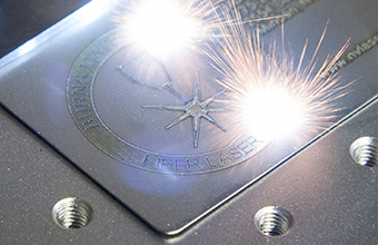 A picture of a metal business card being etched